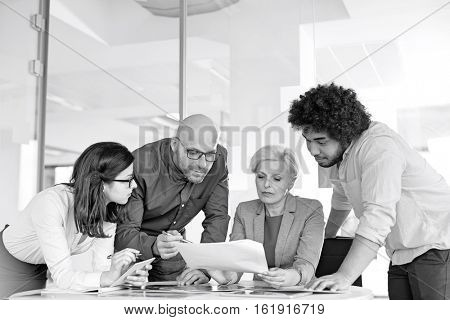 Multi-ethnic business people discussing over document at table in office