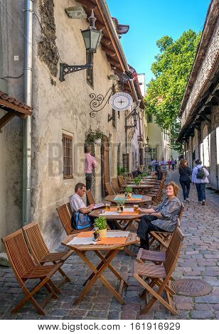Tallinn, Estonia - August 2, 2011: Street cafe on one of the streets of Upper Town. Cafe tables are right on the narrow street, visitors drink beer.