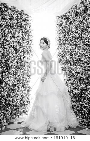 Side view portrait of smiling bride standing amidst flower decorations