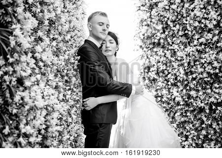 Side view of romantic wedding couple with eyes closed embracing amidst flower decorations