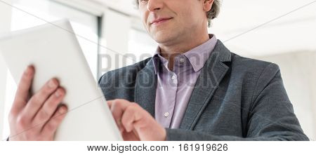 Mature businessman using tablet computer in new office