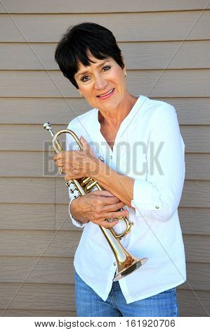 Mature female jazz trumpet player expressions outdoors.