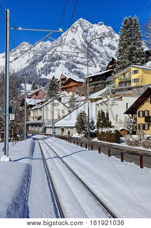 Engelberg, Switzerland - 9 March, 2016: railroad and buildings along Dorfstrasse street, mountains in the background. Engelberg is a resort town and municipality in the Swiss Canton of Obwalden.