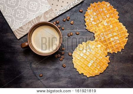 Waffles with coffee beans and honey on rustic wood background. Belgian waffles and cup of coffee on wood table background