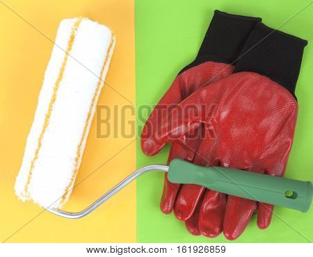 Paint roller and red nitrile gloves on a colorful background