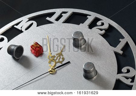 game in a thimble on the clock with a New Year gift