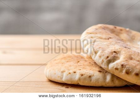 Pita Arabic bread soft baked flatbreads on wooden background selective focus