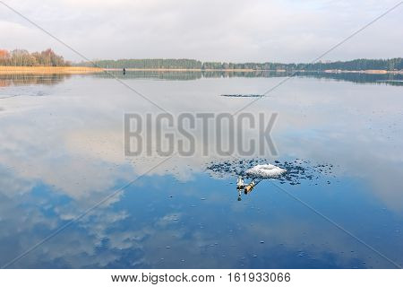 Ice fishing rod on frozen lake covered with a layer of water