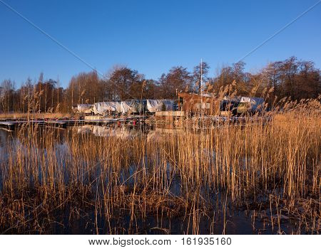 Winter landscape scenery in Helsinki Finland with Baltic Sea and marina and boat in winter storage covered by tarpaulin on the background on 27 December 2015