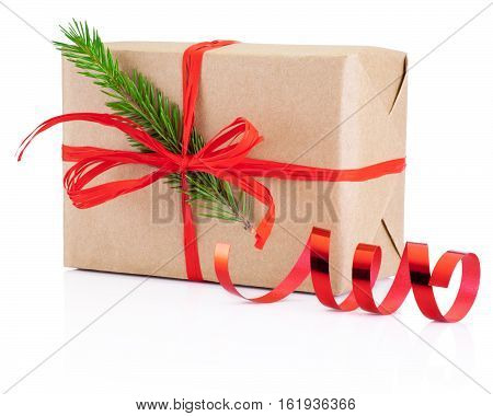 Christmas gift in kraft paper tied red braid and pine tree branch Isolated on white background