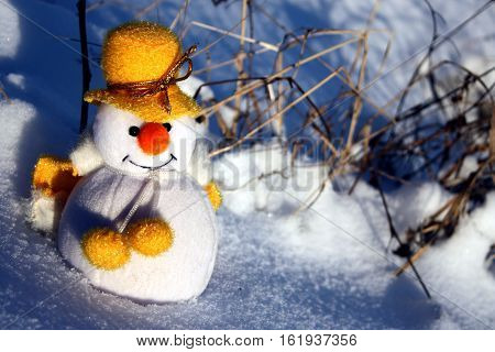 Happy cute snowman wishing Merry Christmas and a Happy Bew Year on natural snow and plants background