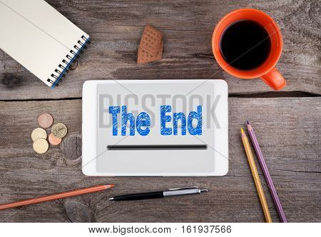 The End. Text on tablet device on a wooden table