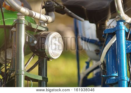 Close up of old mopeds of green and blue colors