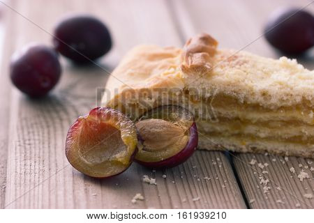 sweet pie with plum on wooden table