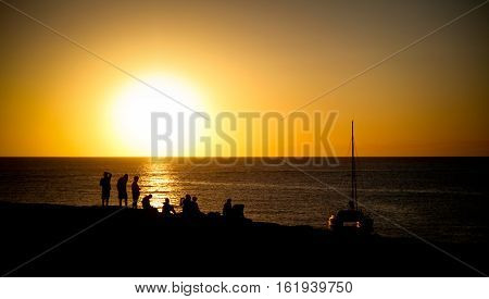 Several people watching the sunset over the mediterranean sea from a cliff on the island of Formentera