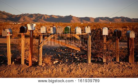 Several mailboxes in the desert during sunset