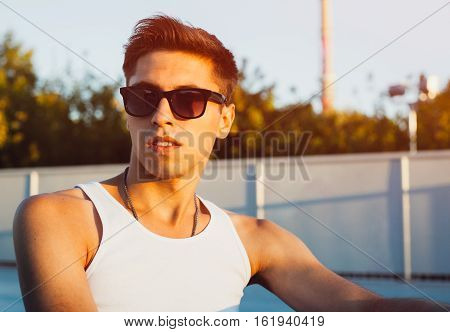 Young handsome man outdoor portrait. Dressed wearing white shirt, suglasses. Fashion gay on street palm at sunset. Ouutdoor.