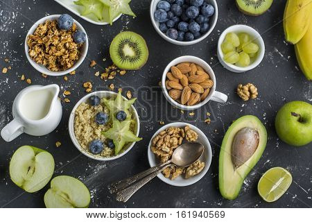 Ingredients for a healthy breakfast, avocado, quinoa bowl, carambola, green apple, banana, kiwi, nuts, oatmeal, berries fruits blueberry almonds walnuts Top Greenery