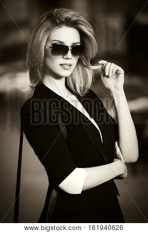 Young business woman walking on city street. Stylish fashion model in sunglasses outdoor
