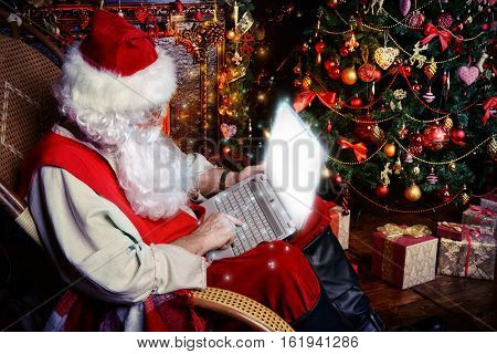 Traditional Santa Claus at his house surfing in the Internet with his laptop. Christmas time. Christmas decoration.