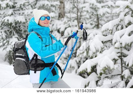 Woman Smiling In Winter Forest Holding Ski Poles.