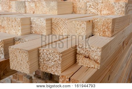 Close-up of unevenly protruding sawn rectangular wooden pine blocks . At the ends of visible tree fiber.