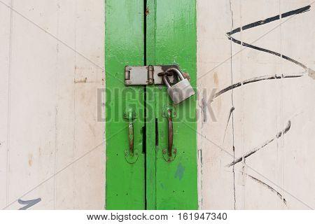Old wooden paint green door with padlock