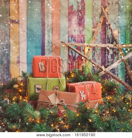Christmas gifts bundled up in a tree on wooden background