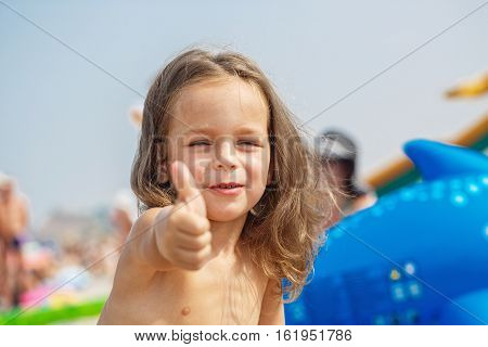 Very cute child showing super sign on the beach