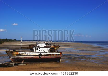 a left and old fishing boat on the coast of the Pacific at low tide buried in the sand on a background of blue sky in Mozambique