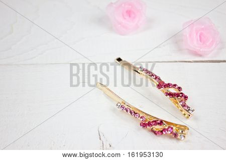 Golden hairpins with pink gemstone and pink roses on white wood
