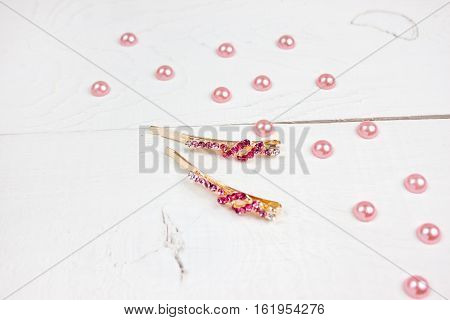 Golden hairpins with pink gemstone and pink pearls on white wood