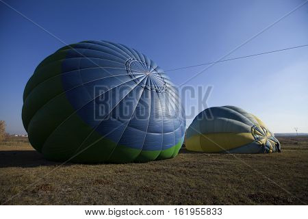 Inflating two air balloons on the field in autumn