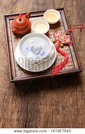Tang Yuan(sweet dumplings) filled with black sesame and teapot on wooden table. Traditional cuisine for lantern festival Mid-autumn festival Dongzhi (winter solstice festival) and Chinese new year. poster