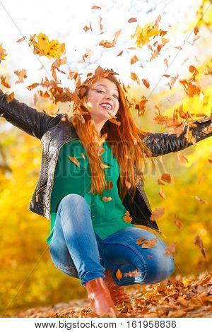 Nature outdoor playing relax leisure concept. Crazy girl throwing leaves. Euphoric redhead woman tossing around autumnal foliage having time of her life.