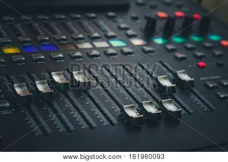 The audio equipment control panel of digital studio mixer side view. Close-up selected focus