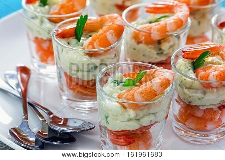 individual Cocktail Shrimp shot glasses with delicious homemade tartar spicy sauce decorated with parsley leaf on white platter on table mat for Christmas dinner or cocktail party close-up