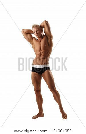 Young fair male gymnast in sexy shorts posing and showing his musculs with his arms up