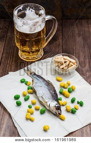 Dried fish, roach with a glass of cold beer on a wooden table