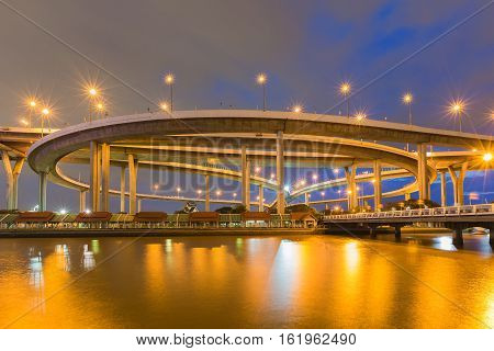 Twilight sky over Highway overpass intersection with reflection lights night view