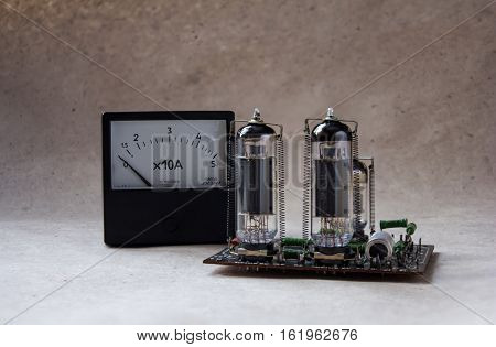 composition from of tube amplifier and vintage ammeter. electronic background