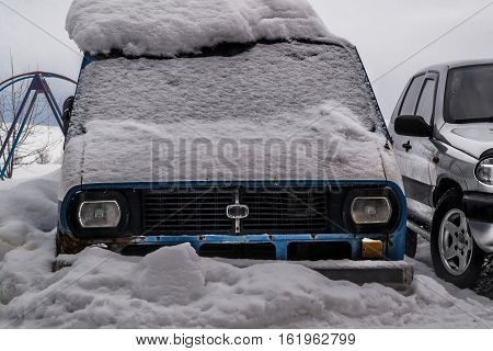 Old minibus. Old rusty minibus covered with snow. Wagon. Rusty car