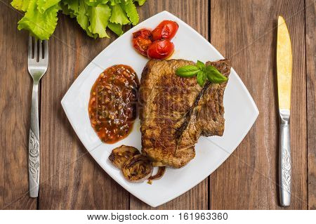 Rare Beef steak medium grilled with barbecue sauce. Wooden table. Top view. Close-up