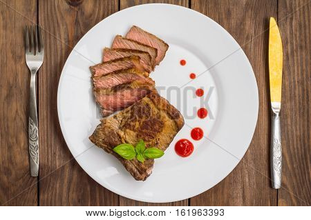 Rare Beef steak medium grilled with barbecue sauce. Wooden table. Top view