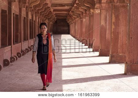 Young woman walking in colonnade walkway at Fatehpur Sikri, Agra, Uttar Pradesh, India. A UNESCO World Heritage site.