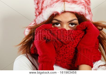 Fashion snowy time people concept. Woman with red winter clothing. Mulatto model wearing warm cap and scarf