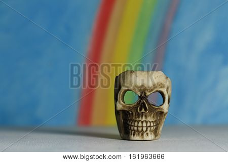 Human skull with a blue sky and rainbow background, a symbol of death, horror and vanitas; landscape format.