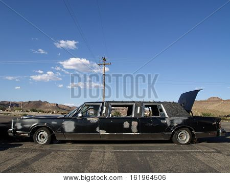 Old abandoned long black limousine wreck in a parking place