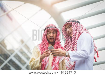 Two Arab Or Muslim Business Man Standing At Front Modern Office Discussing Work With Smart Phone. Et