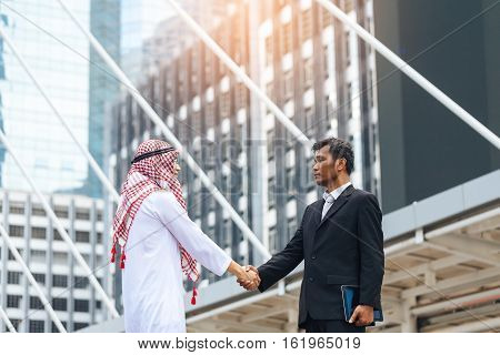 Business Success Concept. Asian Muslim Businessman And Engineer Man Making Handshake Or Holding Hand